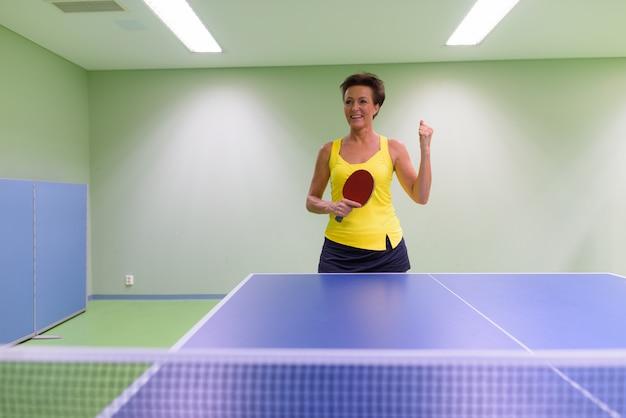 屋内で卓球をしている成熟した美しい女性