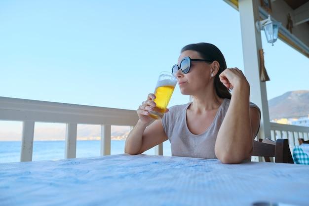 차가운 맥주 한 잔을 마시는 바다 카페에 앉아 쉬고 성숙한 아름 다운 여자. 여름 방학, 여성은 바다 일몰 풍경과 맛있는 음료, 복사 공간을 즐깁니다.