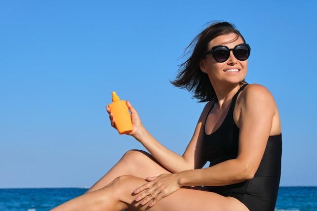 日焼け止めクリームを使用してビーチに座っている成熟した美しい女性は、中年女性の美しさと健康をケアします。夕日の背景に青い空と海