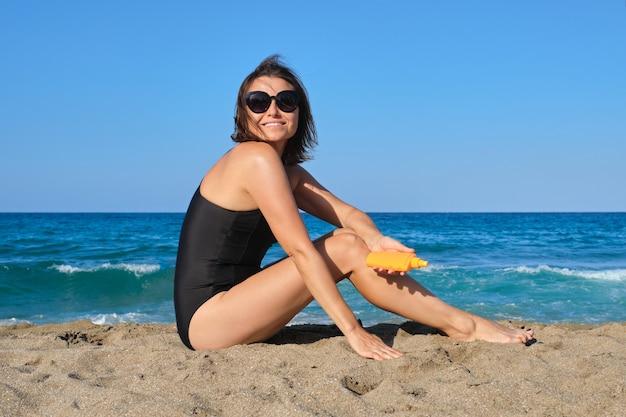 태양 보호 크림을 사용하여 해변에 앉아 성숙한 아름다운 여인