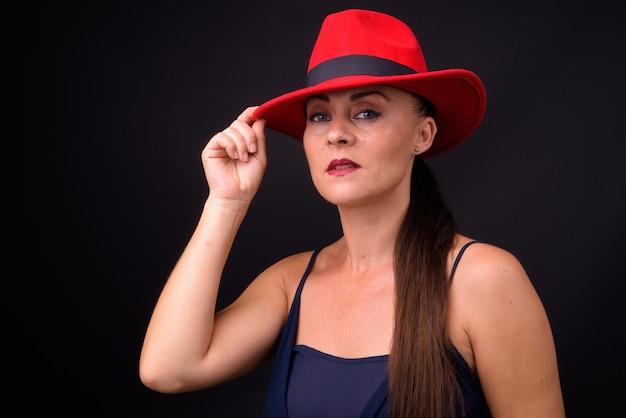 黒い壁に赤いフェドーラ帽をかぶった成熟した美しい女性