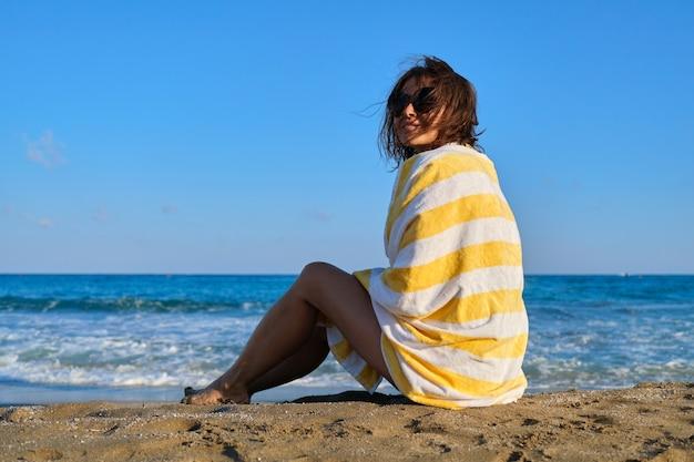 砂の上に座ってビーチタオルで成熟した美しい女性、海の夕日の風景を楽しんで幸せな笑顔の女性。リラックス、レジャー、美しさ、海、中年のライフスタイル