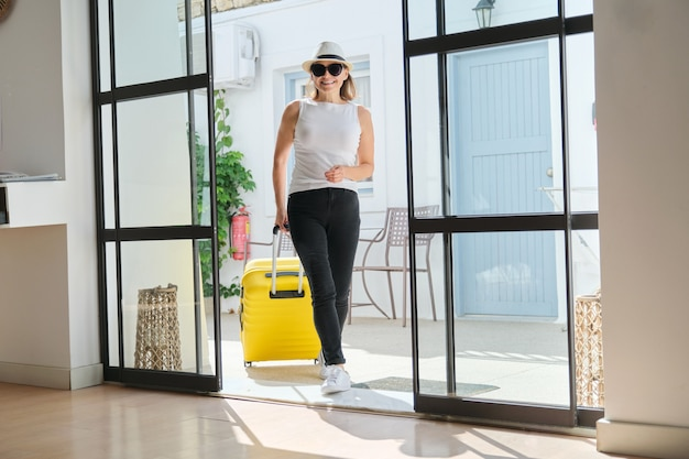 Mature beautiful woman with suitcase in lobby of modern spa resort hotel