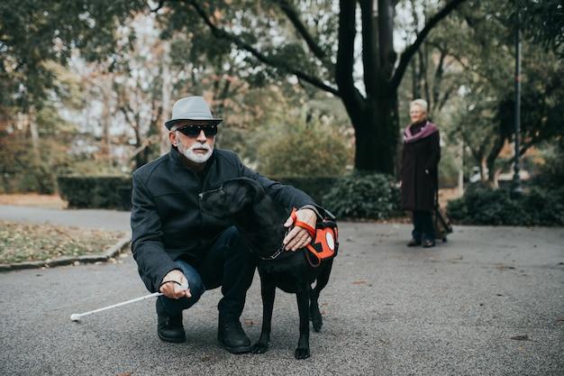 그의 안내견과 함께 공원에서 즐기는 긴 흰색 지팡이와 성숙한 시각 장애인.
