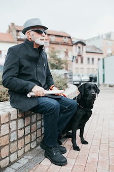 Mature blind man with his guide dog sitting on street.