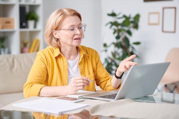 自己隔離でリモート作業中にビデオチャットを使用しながらラップトップの前に机のそばに座っている成熟した金髪の実業家