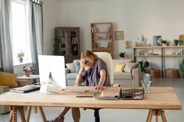モニターの前のテーブルのそばに座って、自宅でオンライン映画を見ながらコンピューター画面の前で笑っている成熟した金髪の陽気な女性