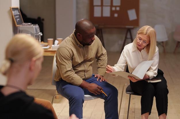 Зрелая блондинка-психолог женщина в элегантной повседневной одежде сидит на стуле рядом с пациентом-африканцем и показывает ему личные документы