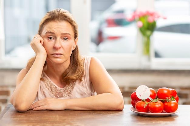 食物アレルギーと敏感な感じを持っているテーブルに座っている成熟したブロンドの髪の女性
