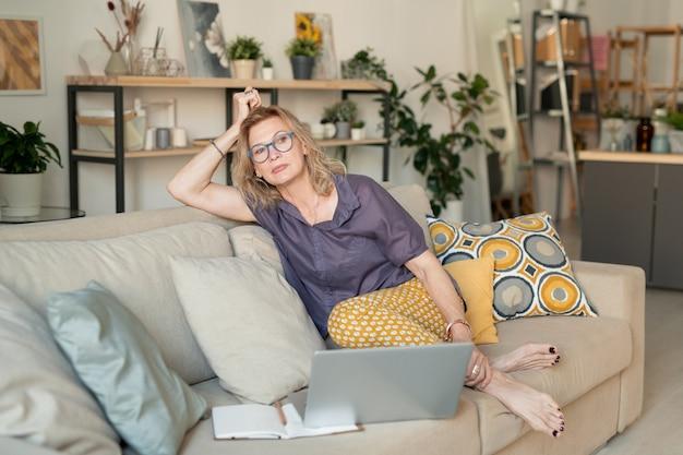 ノートパソコンの前のソファに座って、家庭環境での仕事中に考えているカジュアルウェアで成熟した金髪のリラックスした実業家