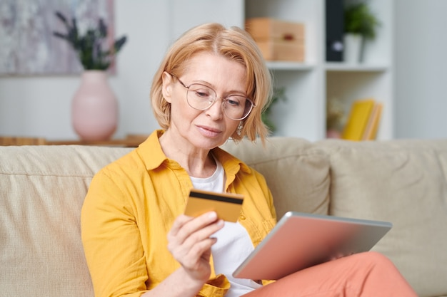 Mature blond woman in eyeglasses and casualwear looking at credit card while going to do online shopping during home quarantine
