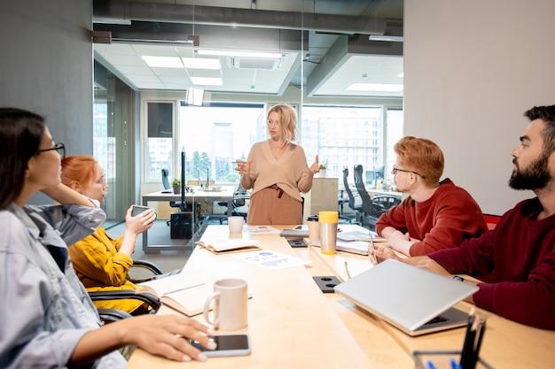 Зрелая блондинка в повседневной одежде стоит за столом перед своими молодыми межкультурными коллегами во время бизнес-тренинга в офисе