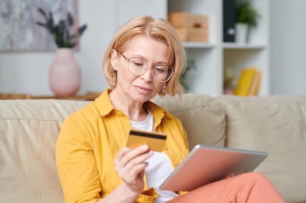 自宅の検疫中にオンラインショッピングをしながらクレジットカードを見ている眼鏡とカジュアルウェアの成熟したブロンドの女性