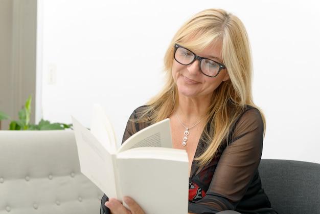 Mature blond woman reading a book