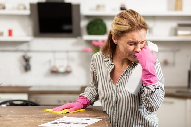 週末にくしゃみとアレルギーに苦しんでいる成熟したブロンドの髪の主婦