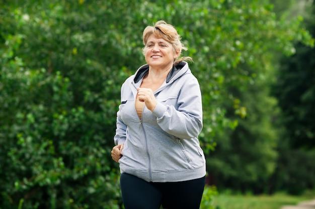 Зрелая блондинка бегает в парке по тропинке
