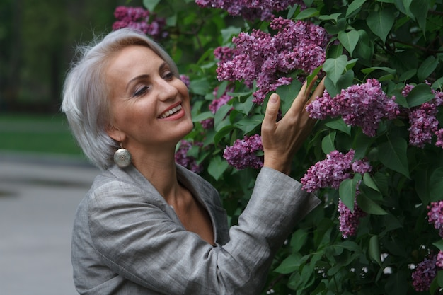 Mature blonde woman in gray suit walks in public garden, admires flowers and smiles