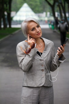 Mature blonde woman in gray suit walks in public park, listens to music with headphones and smiles