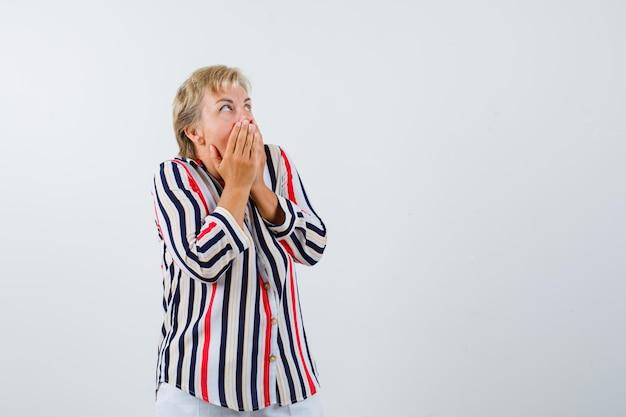 Зрелая блондинка в рубашке в вертикальную полоску
