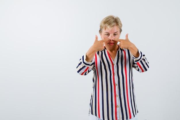 세로 줄무늬 셔츠를 입은 성숙한 금발의 여자