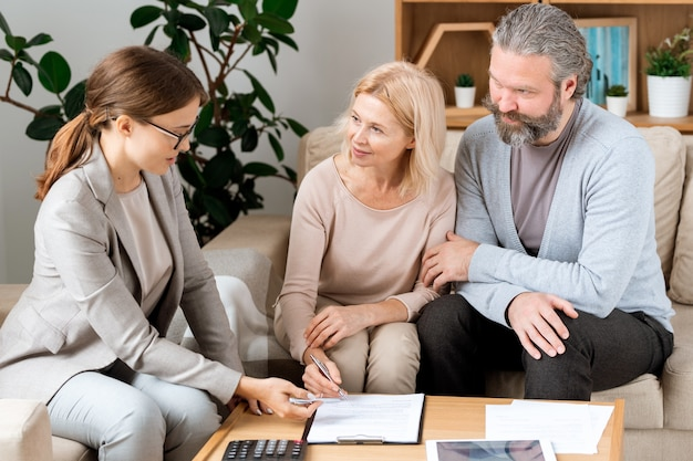 Mature blonde woman listening to young confident real estate agent while going to sign contract in office