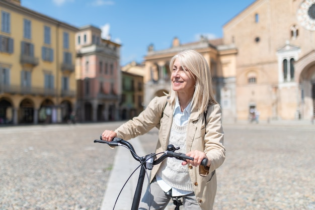 Mature blonde woman riding her bike in a city