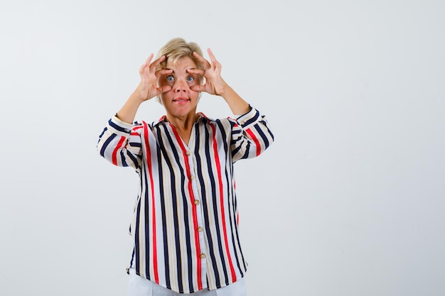Donna bionda matura con una camicia a righe verticali