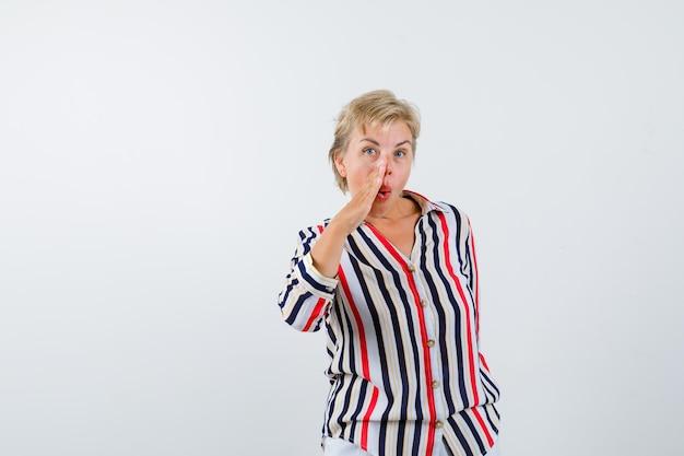 Mature blonde woman in a vertical-striped shirt