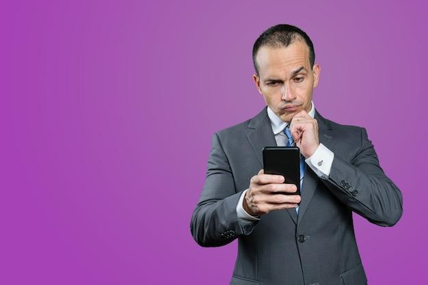 成熟したブラジル人男性、正装で、スマートフォンを手に、優柔不断な顔をしています。紫の背景。