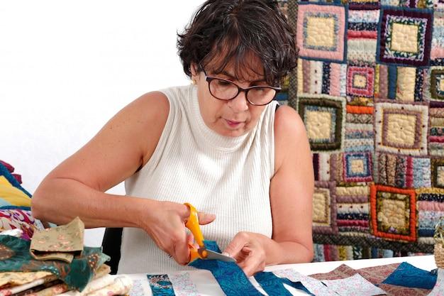 Зрелая брюнетка женщина режет ткань для пошива пэчворка