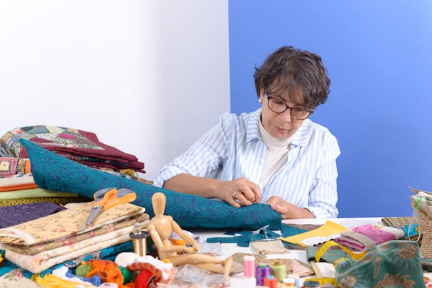 Mature brunette woman sewing patchwork