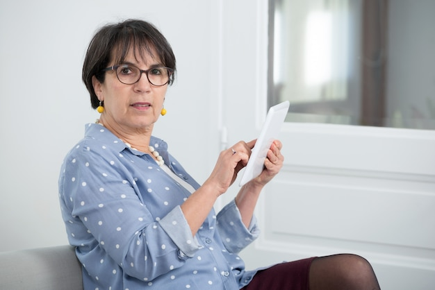 Mature brunette woman sitting on sofa using digital tablet