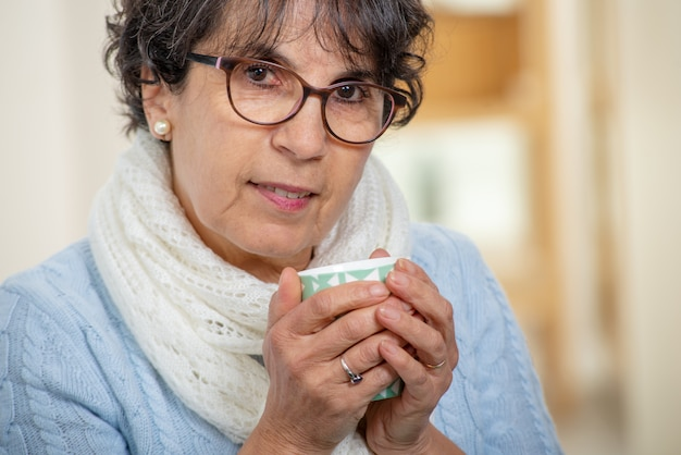 Mature brunette woman with glasses drinking cup of tea