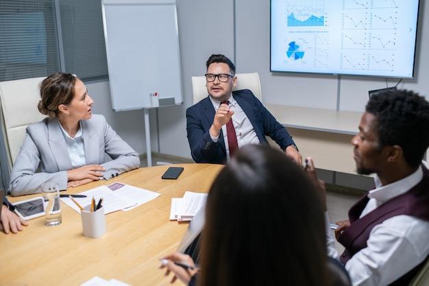 若いマネージャーと話している成熟したビジネスコーチ