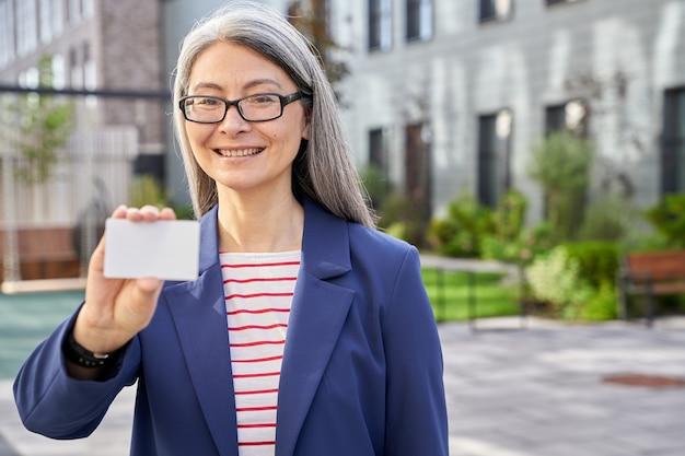 빈 플라스틱 카드를 들고 웃고 있는 성숙한 비즈니스 여성