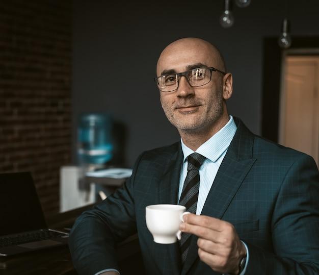 Зрелый деловой человек в деловом костюме, держа чашку кофе в кафетерии офисного здания