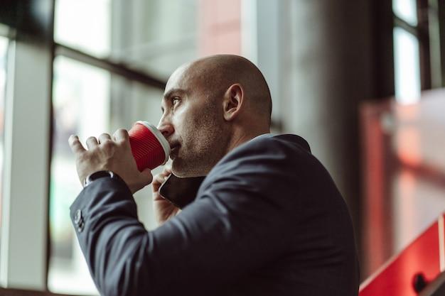 Зрелый деловой человек в деловом костюме, разговаривает по телефону, попивая кофе, используя одноразовые