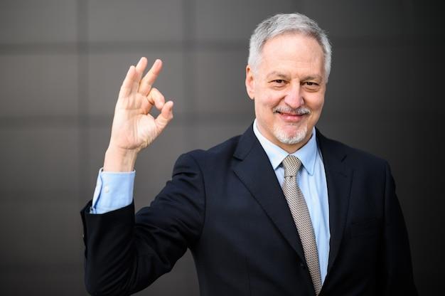 Портрет зрелого делового человека на открытом воздухе, делая знак хорошо рукой