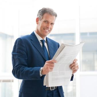 成熟したビジネスの男性がニュースを読んで、カメラに笑顔