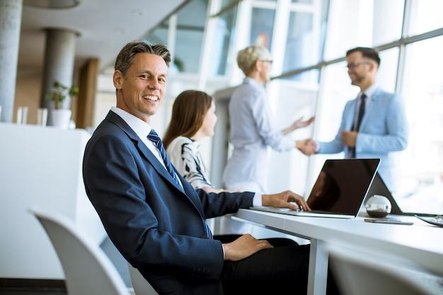 Зрелый бизнесмен работая на компьтер-книжке пока его партнеры смотря результаты дела в офисе