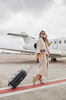 Mature business woman in coat near her jet in airport