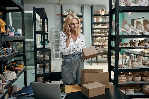 Зрелая деловая женщина, предприниматель разговаривает с клиентом по телефону, держа картонную коробку