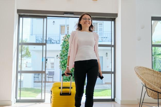 Зрелая деловая женщина в интерьере отеля с чемоданом, женщина, путешествующая с деловой поездкой
