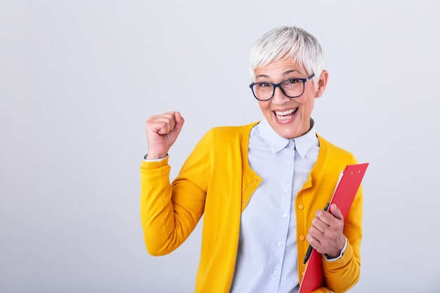Mature business woman with clipboard in hands celebrating business deal or win. portrait of corporate woman looking excited sign in creative success and happiness at work concept