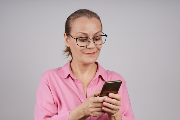 성숙한 비즈니스 여자 안경, 핑크 블라우스에 휴대 전화를 사용하여 메시지를 입력합니다. 회색 배경에 고립 된 사진입니다.