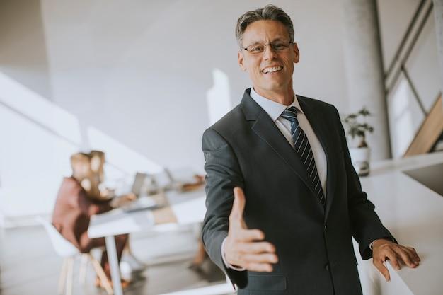 Зрелый бизнесмен приближается и предлагая руку для рукопожатия в офисе
