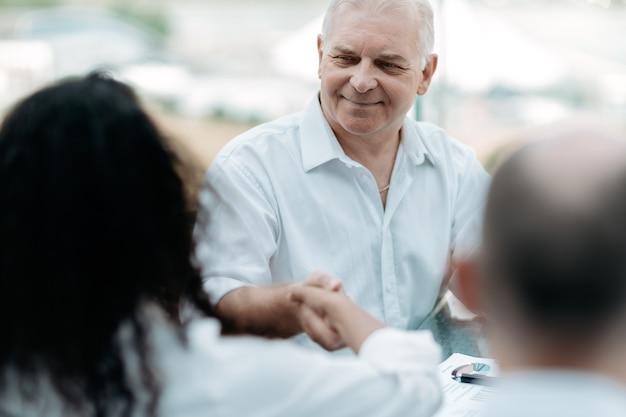 成熟したビジネスマンは彼のビジネスパートナーと自信を持って握手します