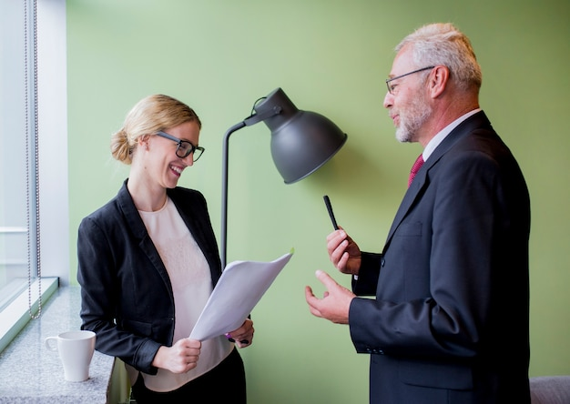 Mature businessman discussing with smiling young businesswoman