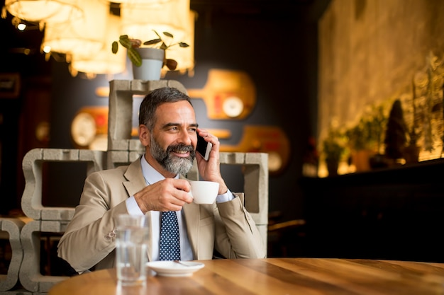 Mature businessman drinking coffee in cafe and using mobile phone