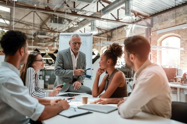 オフィスのオフィスのテーブルに座って同僚に何かを説明する成熟したビジネスマン